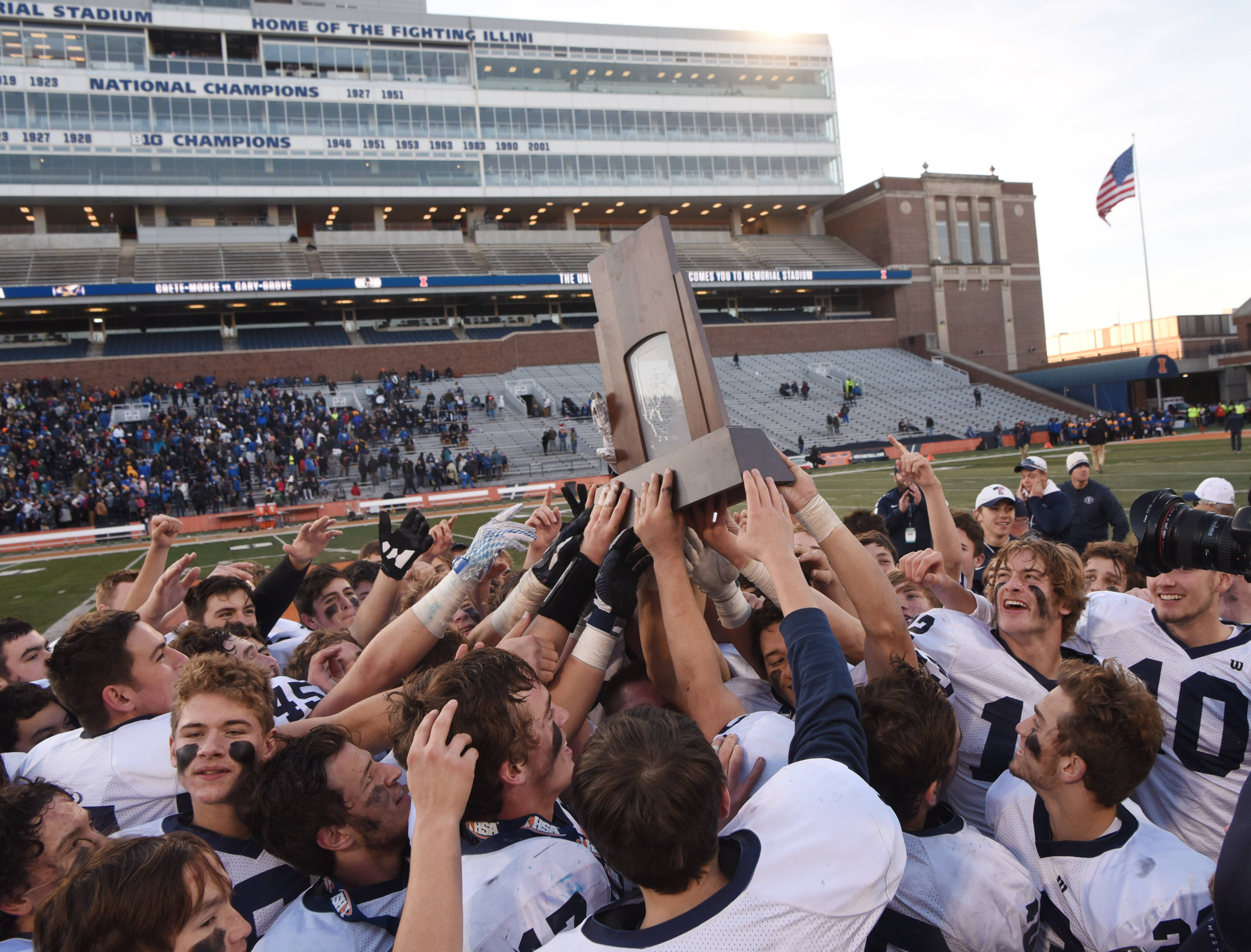 Cary-Grove celebrates with its trophy following the Trojans' 35-13 victory over Crete-Monee in the Class 6A state football championship at Memorial Stadium in Champaign Saturday.