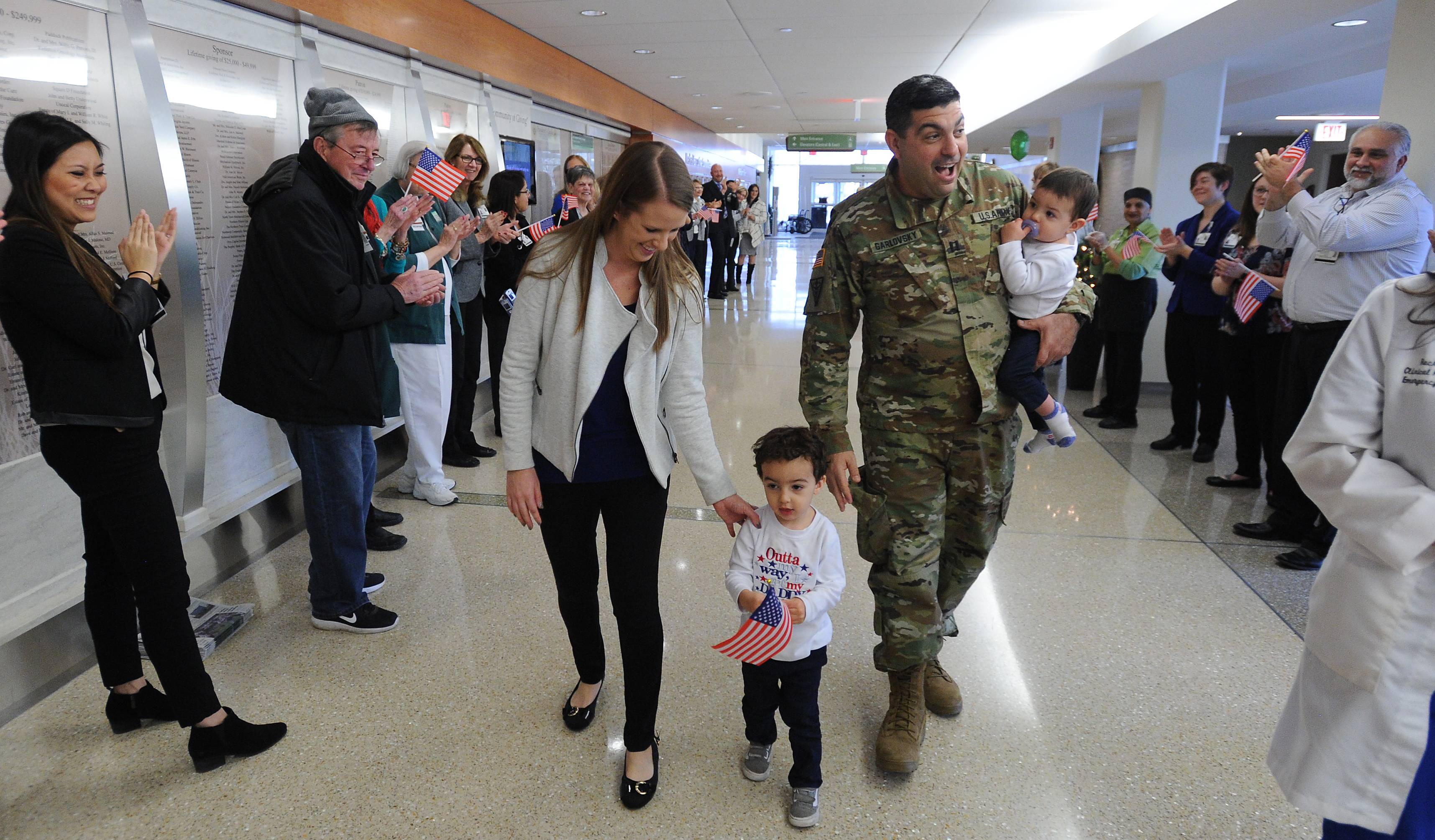 Northwest Community Hospital employees line the main hallway for the return of Dr. Jonathan Garlovsky on Monday. The U.S. Army Reserve captain arrived with his wife, Trisha, and sons Mason, 2, and Nate, 1.