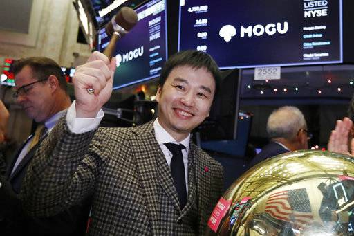 Mogu Inc. co-founder, Chairman and CEO Shark Chen rings a ceremonial bell as his company's IPO begins trading on the floor of the New York Stock Exchange, Thursday, Dec. 6, 2018.
