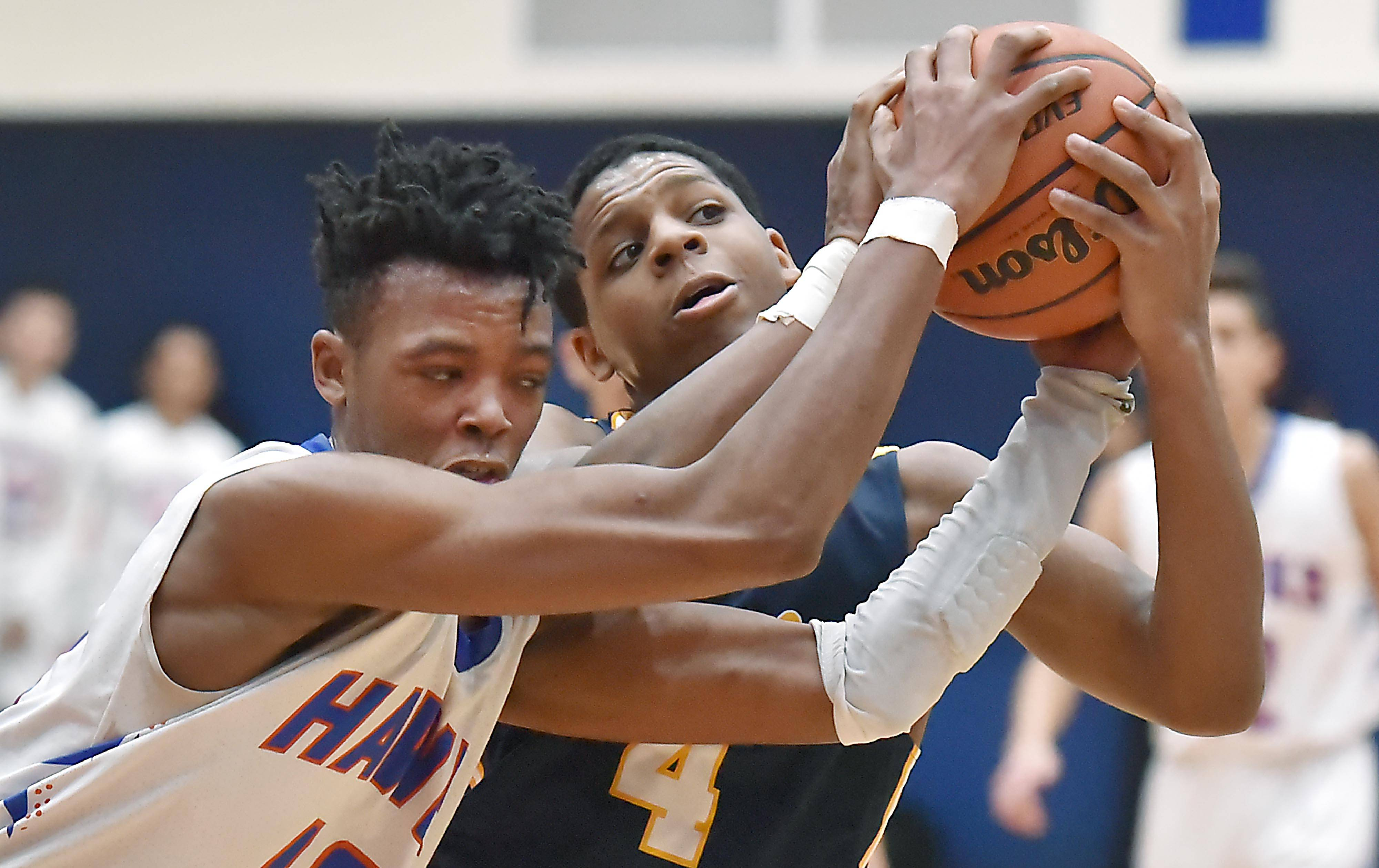 Round Lake's Hakim Williams and Hoffman Estates' Sheldon Barnett-Morales fight for possession of the ball Wednesday in a boys basketball game in Hoffman Estates.