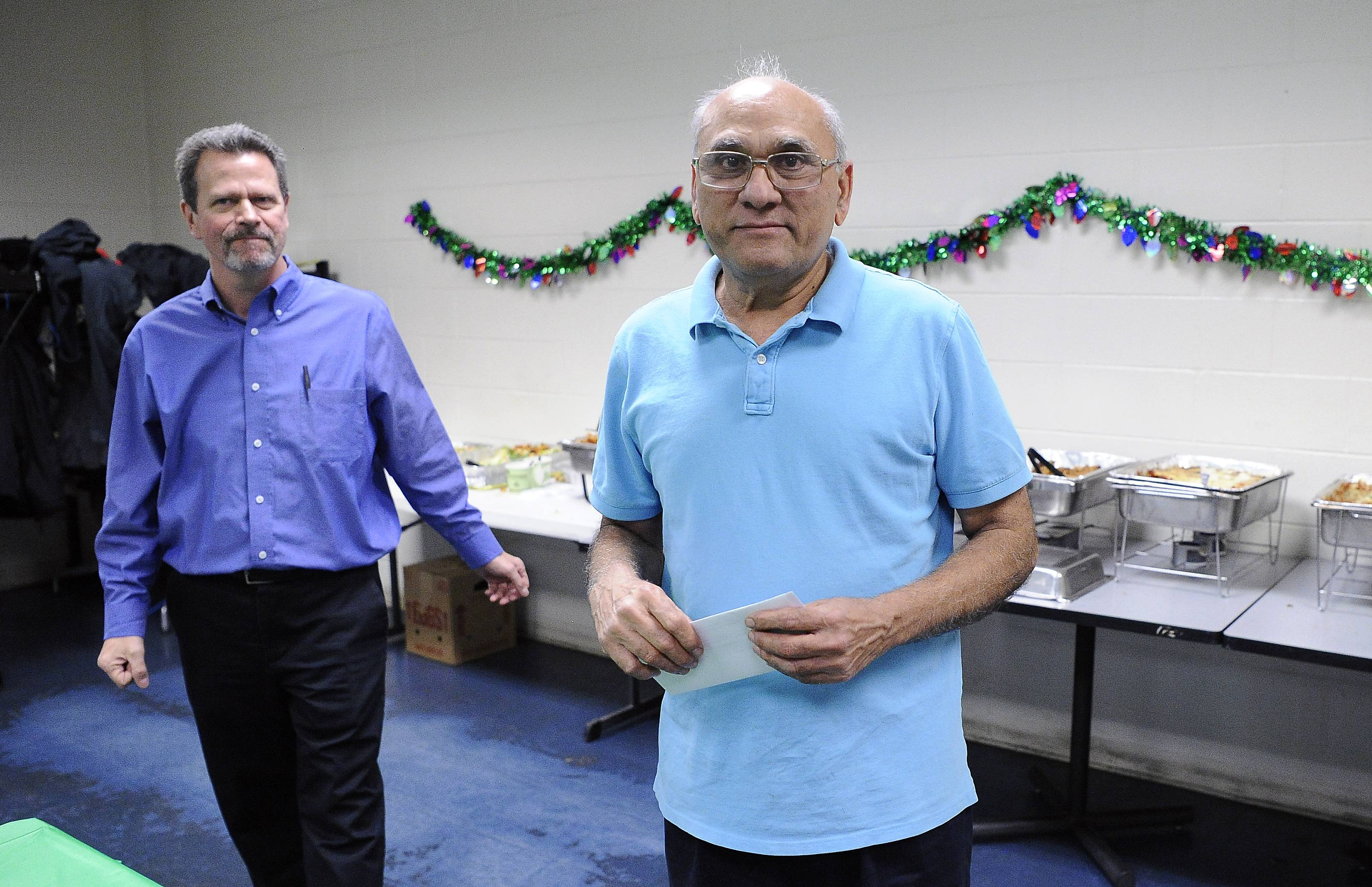 Director of Production Don Stamper, left, congratulates Rameshchandra Patel, who won the award of excellence for part-time employee, at an awards luncheon at the Daily Herald Printing Center.