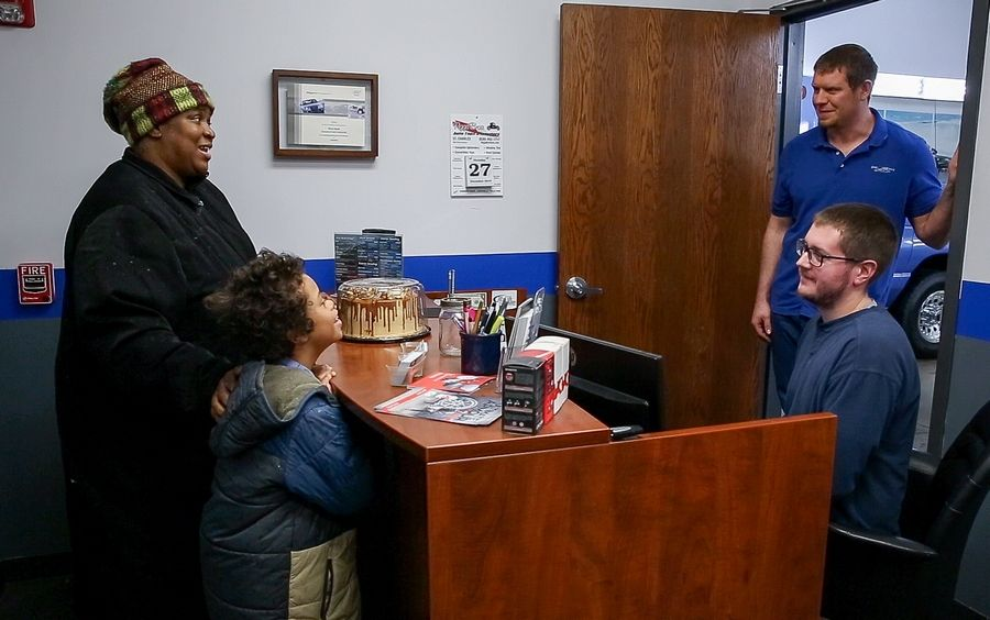 Helen Hines of Oak Park and her 10-year-old son, Ahshawn Reed, bring a thank-you cake to technician Brendon Hedlund, left, and manager Dave Baker at Rush Group Detailing in St. Charles on Thursday. The business cleaned her car at no cost.