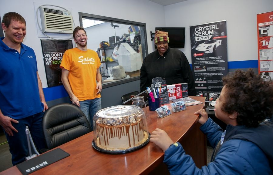 Helen Hines of Oak Park and her son, Ahshawn Reed, 10, stopped by Rush Group Detailing in St. Charles on Thursday to thank technicians Brendon Hedlund, left, and Will Shanel for completing $260 worth of detailing work on the house.