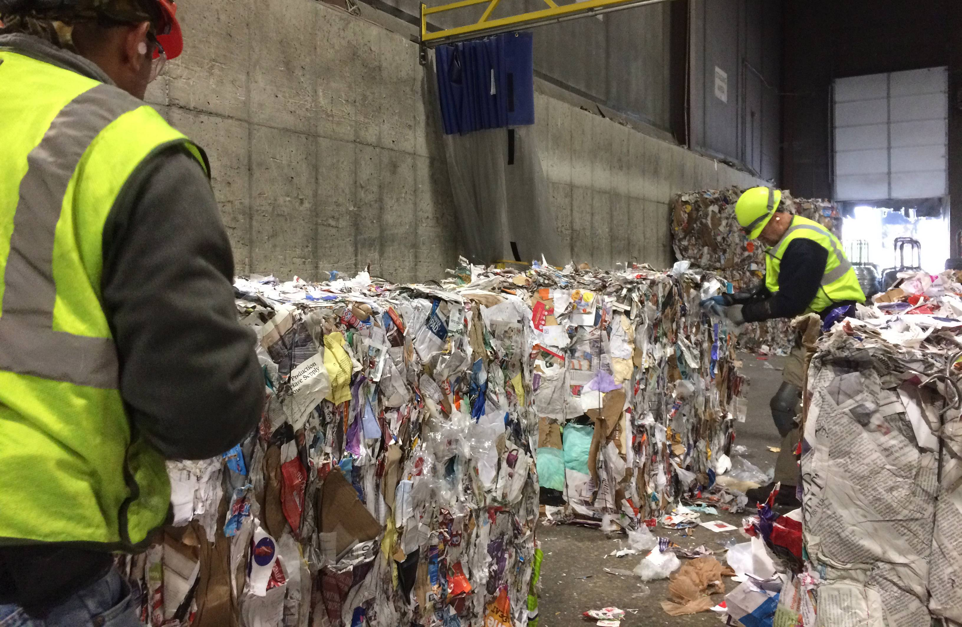 Workers examine one-ton bales of mixed paper for contaminants, such as plastic bags, at the Waste Management processing facility in Grayslake.