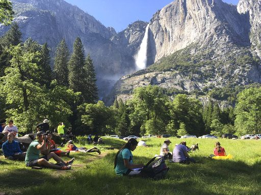 FILE - In this May 25, 2017 file photo, a class of eighth-grade students and their chaperones sit in a meadow at Yosemite National Park, Calif., below Yosemite Falls. Some of the West's iconic national parks are beginning to partially close as they deal with overflowing restrooms and vandals on the 10th day of a federal government shutdown.