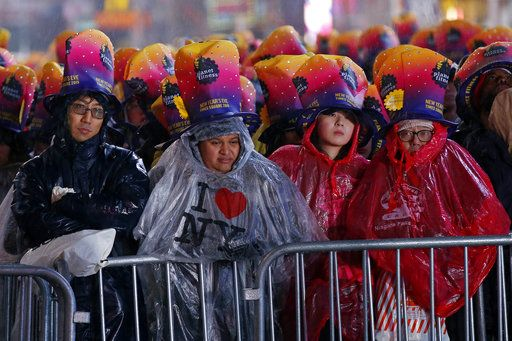 Revelers wait in the rain in New York's Times Square, Monday, Dec. 31, 2018, as they take part in a New Year's Eve celebration.