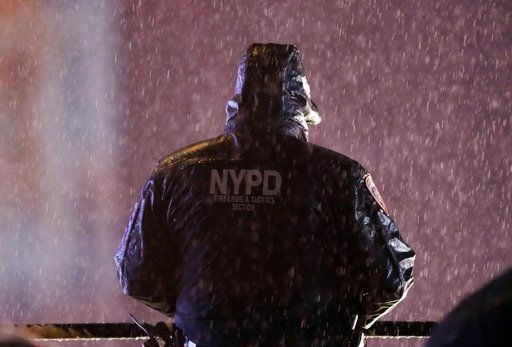 A member of the New York Police Department watches over revelers as they wait for midnight during the New Year's Eve celebration in New York's Times Square, Monday, Dec. 31, 2018, in New York.