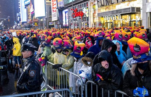 A New York City police officer stands near revelers gathered at Times Square in New York, Monday, Dec. 31, 2018, as they take part in a New Year's Eve celebration.