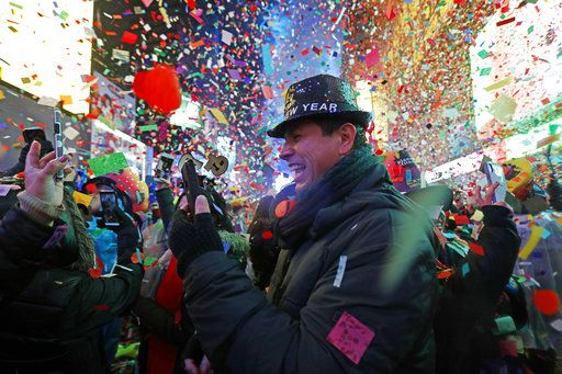 Joey Flores, of California, uses his cellphone as confetti falls during a New Year's celebration in New York's Times Square, Tuesday, Jan. 1, 2019.
