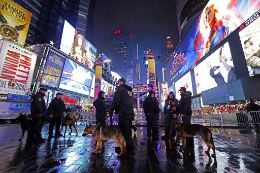 New York City K-9 officers stand near revelers gathered in Times Square in New York, Monday, Dec. 31, 2018, as they take part in a New Year's Eve celebration.