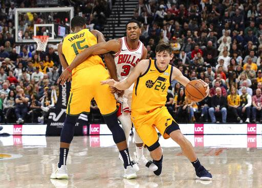 Utah Jazz guard Grayson Allen (24) uses forward Derrick Favors (15) to get away from Chicago Bulls guard Shaquille Harrison (3) during the second quarter of an NBA basketball game Saturday, Jan. 12, 2019, in Salt Lake City.