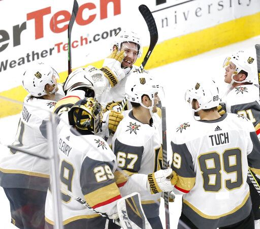 Vegas Golden Knights defenseman Shea Theodore,top center, celebrates with teammates after his goal against the Chicago Blackhawks during the overtime period of an NHL hockey game Saturday, Jan. 12, 2019, in Chicago.