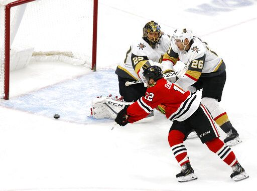 Chicago Blackhawks left wing Alex DeBrincat (12) slips the puck past Vegas Golden Knights goaltender Marc-Andre Fleury (29) for a goal during the first period of an NHL hockey game Saturday, Jan. 12, 2019, in Chicago.