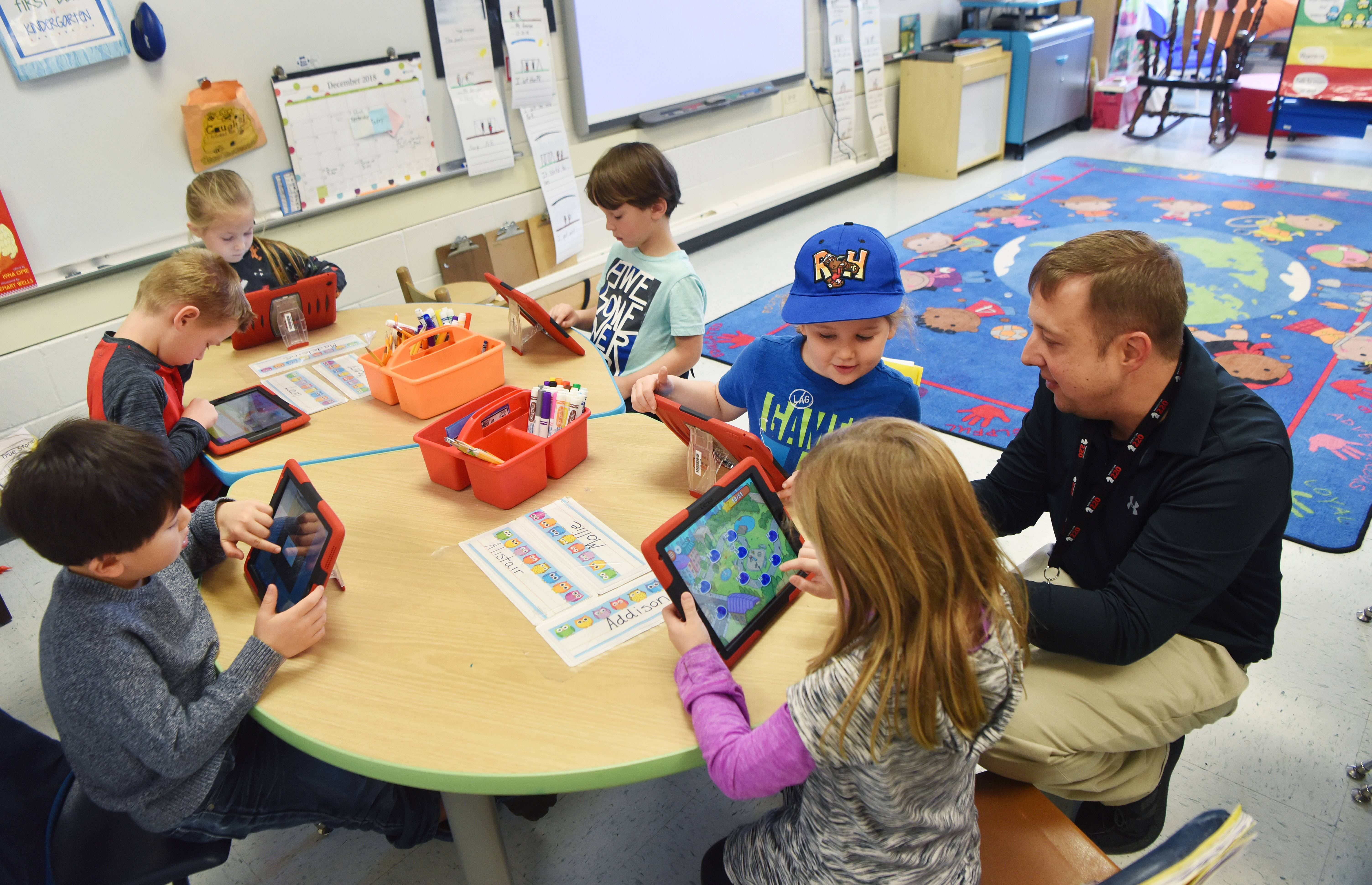 Kindergarten teacher George Vlasis works with a group of his students at Hough Street Elementary School in Barrington. Vlasis recently published his first children's book, written with input from his students.