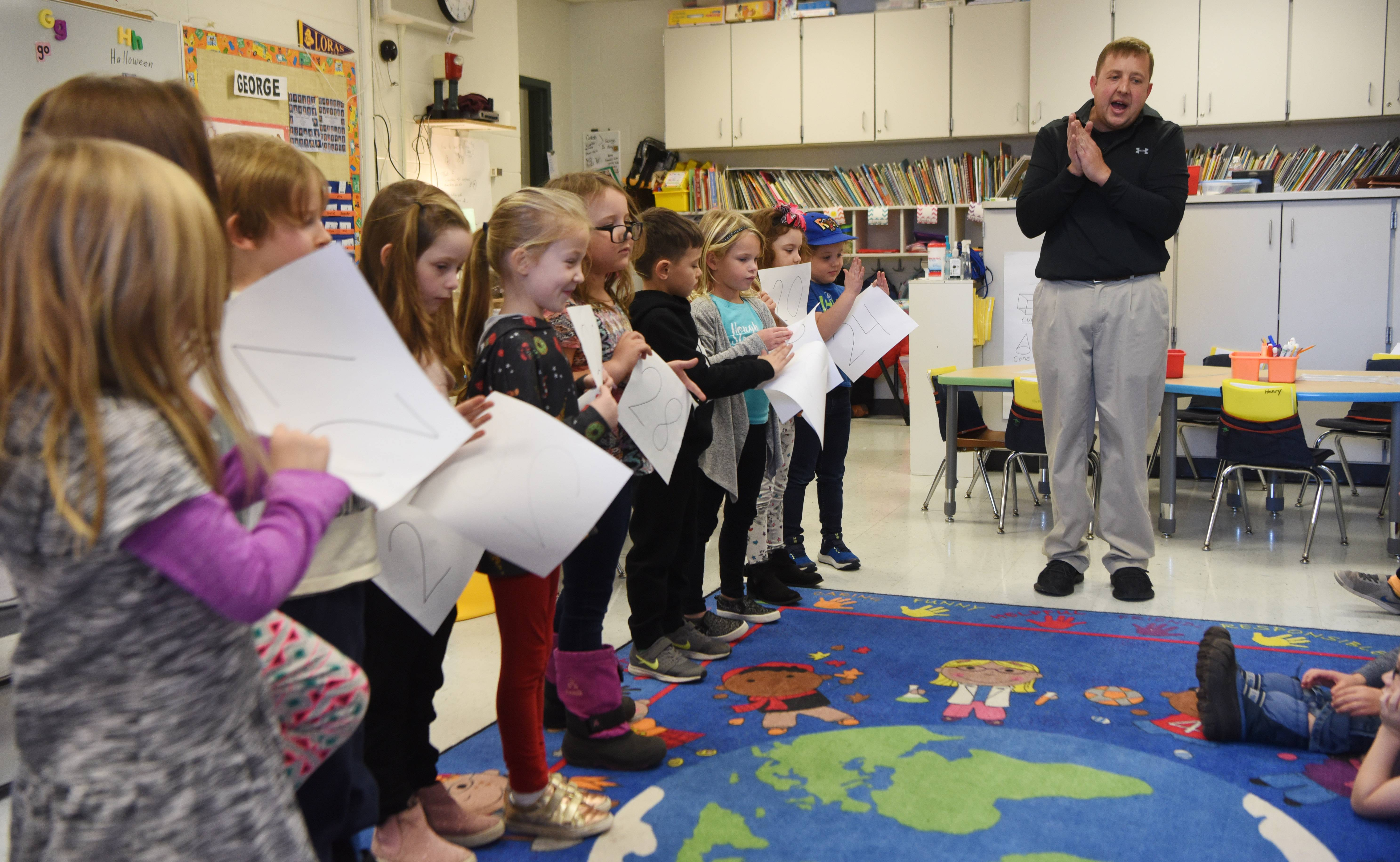 Kindergarten teacher George Vlasis and his students get ready to put two-digit numbers in proper order during their class at Hough Street Elementary School in Barrington.