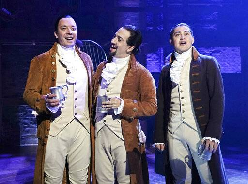 "This image released by NBC shows Jimmy Fallon, host of ""The Tonight Show Starring Jimmy Fallon,"" left, with Lin-Manuel Miranda, center, and a member of the cast from the musical ""Hamilton,"" at the Luis A. Ferré Performing Arts Center in San Juan, Puerto Rico. Fallon will join the cast in a performance of ""The Story of Tonight� from the Tony-winning musical which will air on Fallon's show on Tuesday, Jan. 15.  (Andrew Lipovsky/NBC via AP)"