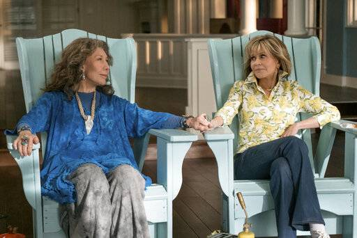 "This image released by Netflix shows Lily Tomlin, left, and Jane Fonda in a scene from the comedy series ""Grace And Frankie."" As the fifth-season adventures of ""Grace and Frankie"" begin, viewers can rest assured there's more to come. Series creator Marta Kauffman and Netflix said Tuesday, Jan. 15, 2019,  that the comedy starring Fonda and Tomlin has been renewed for season six, due in 2020. (Ali Goldstein/Netflix via AP)"