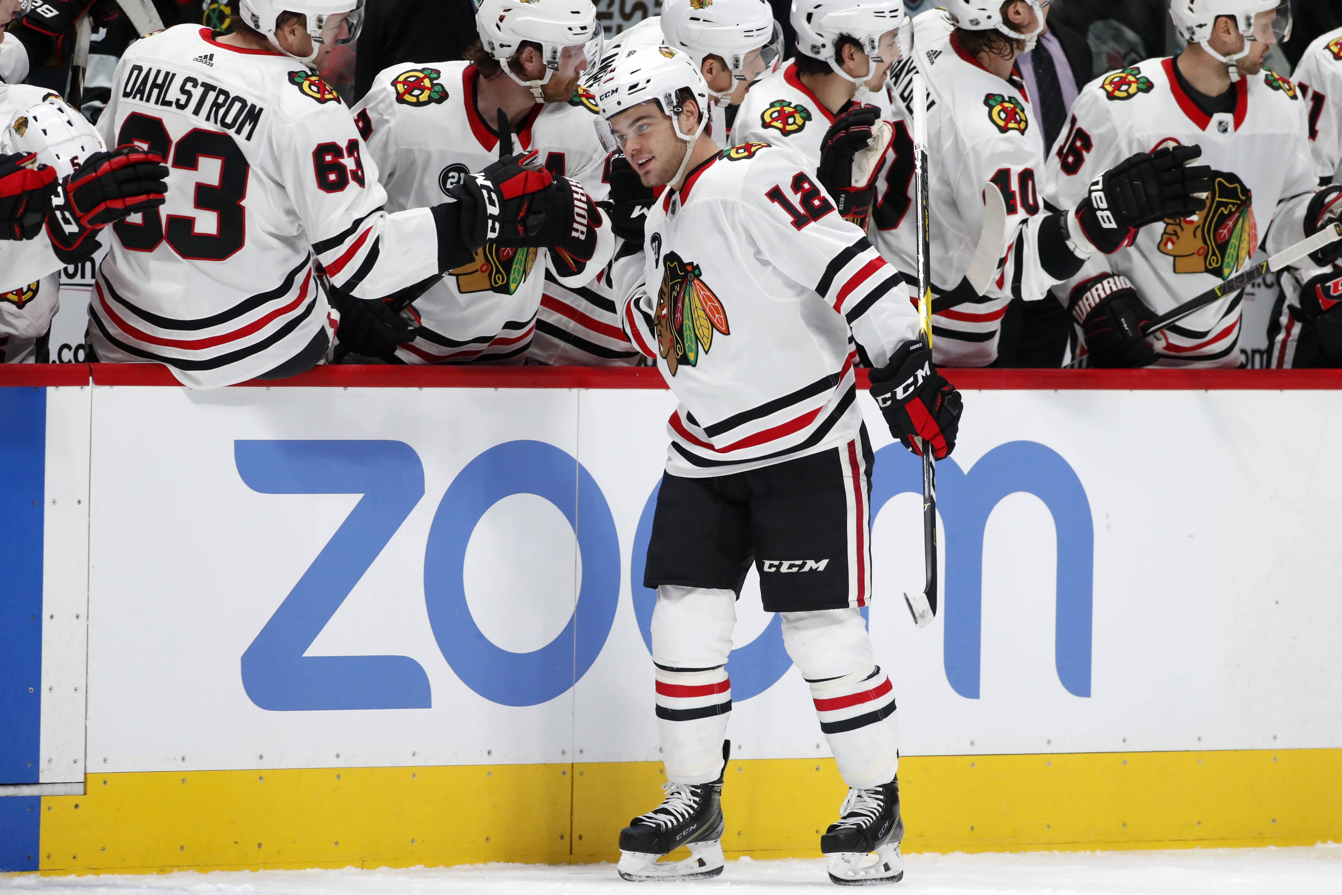 Chicago Blackhawks left wing Alex DeBrincat, front, is congratulated as he passes the team box after scoring a goal against the Colorado Avalanche in the first period of an NHL hockey game Saturday, Dec. 29, 2018, in Denver.