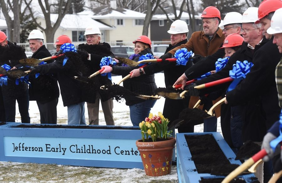 Dignitaries toss dirt with ceremonial shovels during the groundbreaking for a new Jefferson Early Childhood Center in Wheaton.