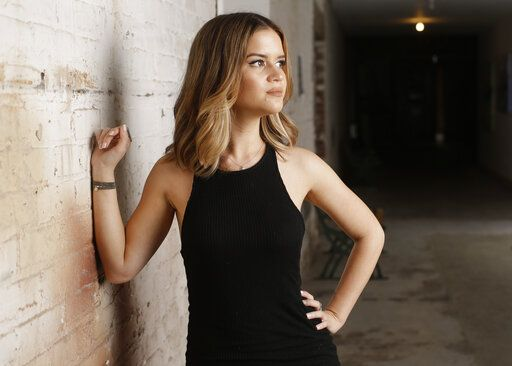 "FILE - In this May 31, 2016, file photo, singer Maren Morris poses in Nashville, Tenn. Morris is nominated in both country, pop and all-genre categories this year, including two nominations in the country genre categories for ""Dear Hate,� a duet with Vince Gill released after the Las Vegas mass shooting, and a nomination for ""Mona Lisas and Mad Hatters,� a cover from an Elton John tribute album. Her song ""The Middle"" with EDM artists Zedd and Grey, is nominated for record and song of the year at this year's Grammy Awards on Feb. 10, and Morris was also nominated for best pop duo/group collaboration."