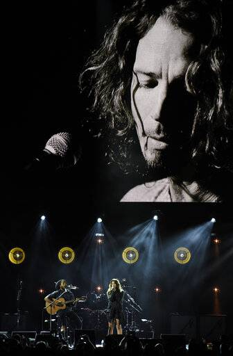 "Toni Cornell, daughter of the late singer Chris Cornell, performs with Ziggy Marley, bottom left, underneath a video image of her father during ""I Am The Highway: A Tribute to Chris Cornell"" at The Forum, Wednesday, Jan. 16, 2019, in Inglewood, Calif. (Photo by Chris Pizzello/Invision/AP)"