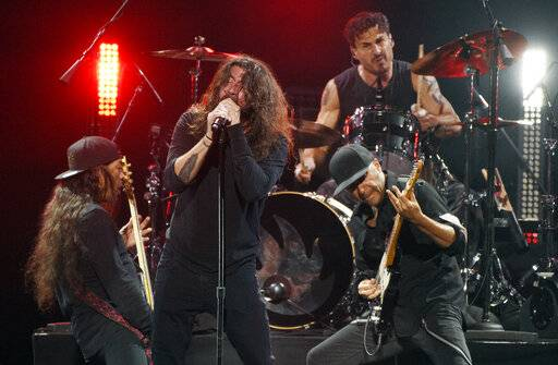 "Dave Grohl, center, performs with Metallica bassist Robert Trujillo, left, and Audioslave members Brad Wilk, top, and Tom Morello during ""I Am The Highway: A Tribute to Chris Cornell"" at The Forum, Wednesday, Jan. 16, 2019, in Inglewood, Calif. (Photo by Chris Pizzello/Invision/AP)"