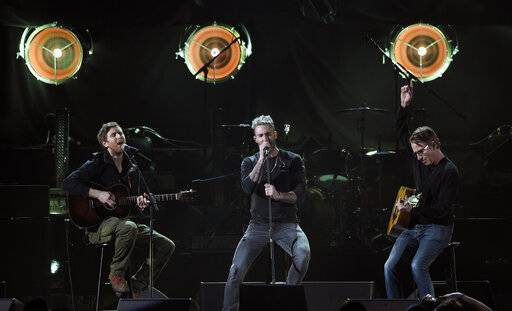 "Adam Levine, center, and Jesse Carmichael, left, of the band Maroon 5 perform with Pearl Jam guitarist Stone Gossard during ""I Am The Highway: A Tribute to Chris Cornell"" at The Forum, Wednesday, Jan. 16, 2019, in Inglewood, Calif. (Photo by Chris Pizzello/Invision/AP)"