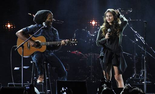 "Toni Cornell, right, daughter of the late singer Chris Cornell, performs with Ziggy Marley during ""I Am The Highway: A Tribute to Chris Cornell"" at The Forum, Wednesday, Jan. 16, 2019, in Inglewood, Calif. (Photo by Chris Pizzello/Invision/AP)"