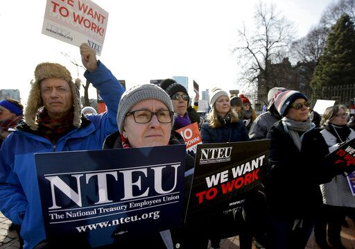 United States Department of Agriculture employee Lori Lodato, of Wilmington, Mass., display placards during a rally by federal employees and supporters, Thursday, Jan. 17, 2019, in front of the Statehouse in Boston, held to call for an end of the partial shutdown of the federal government.
