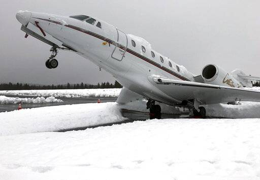 "This Wed. Jan. 16, 2019 photo shows an overnight accumulation of about 20 inches of heavy wet snow dubbed ""Sierra cement"" causing a Cessna Citation X business jet at an outdoor parking spot to do a tail stand at Truckee Tahoe Airport in Truckee, Calif. Airport official Marc Lamb photographed the aircraft before mechanics cleared the snow. No injuries were reported.  (Marc Lamb via AP)"