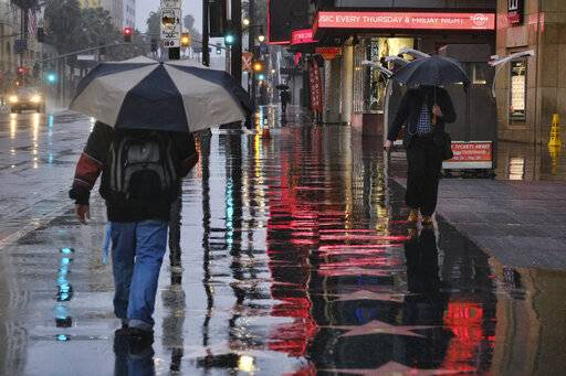Pedestrians make their way along a rain soaked Hollywood Blvd. in Los Angeles on Thursday, Jan. 17, 2019. The latest in a series of Pacific Ocean storms pounded California with rain and snow Thursday, prompting officials to put communities on alert for mudslides and flooding and making travel treacherous.