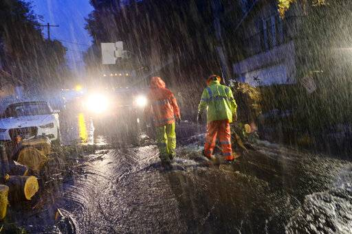 Department of Water and Power employees work in the pouring rain to clear a fallen tree from a road in the Hollywood hills in Los Angeles, Thursday, Jan. 17, 2019. The latest in a series of Pacific Ocean storms pounded California with rain and snow Thursday, prompting officials to put communities on alert for mudslides and flooding and making travel treacherous.