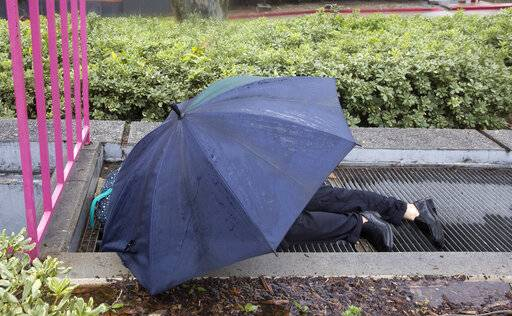 A man sleeps on top of a vent in rain at Grand Park in Los Angeles Thursday, Jan. 17, 2019. Rain and snow fell from one end of the state to the other, canceling flights, uprooting trees, knocking down power lines and causing localized flooding.
