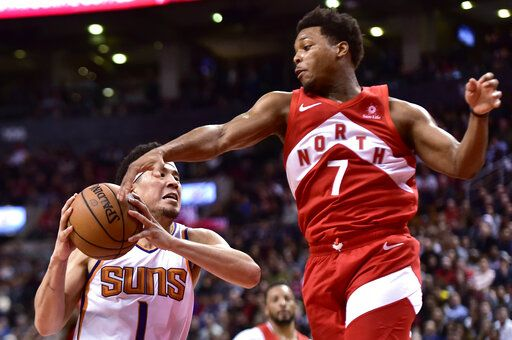 Toronto Raptors guard Kyle Lowry (7) gets a hand to the ball as Phoenix Suns guard Devin Booker (1) drives for the basket during the second half of an NBA basketball game Thursday, Jan. 17, 2019, in Toronto. (Frank Gunn/The Canadian Press via AP)