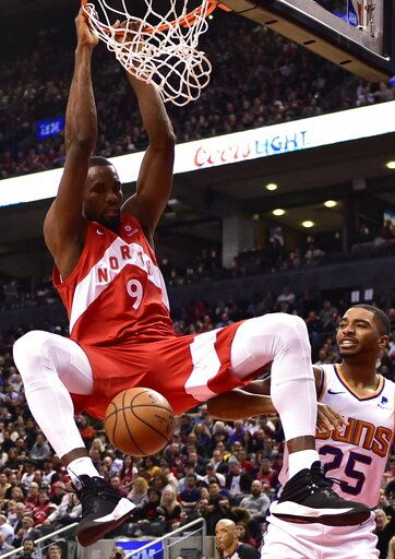 Toronto Raptors forward Serge Ibaka dunks as Phoenix Suns forward Mikal Bridges (25) watches during the first half of an NBA basketball game Thursday, Jan. 17, 2019, in Toronto. (Frank Gunn/The Canadian Press via AP)