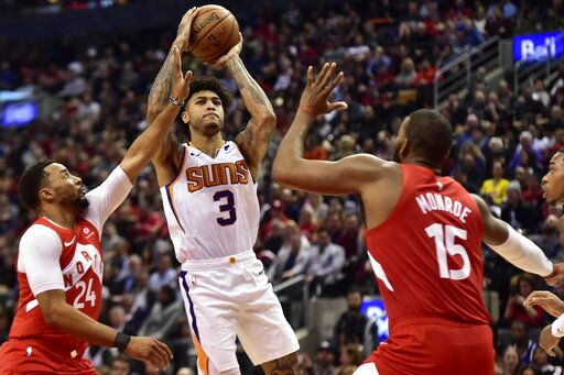 Phoenix Suns forward Kelly Oubre Jr. (3) goes up for a shot as Toronto Raptors forward Norman Powell (24) and center Greg Monroe (15) defend during the second half of an NBA basketball game Thursday, Jan. 17, 2019, in Toronto. (Frank Gunn/The Canadian Press via AP)