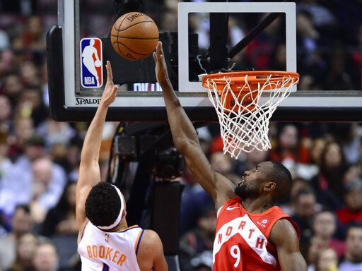 Toronto Raptors forward Serge Ibaka (9) blocks a shot by Phoenix Suns guard Devin Booker during the first half of an NBA basketball game Thursday, Jan. 17, 2019, in Toronto. (Frank Gunn/The Canadian Press via AP)