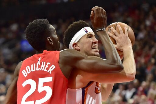 Phoenix Suns guard Devin Booker (1) drives to the basket past Toronto Raptors forward Chris Boucher (25) during the second half of an NBA basketball game Thursday, Jan. 17, 2019, in Toronto. (Frank Gunn/The Canadian Press via AP)