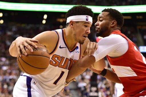 Phoenix Suns guard Devin Booker (1) controls the ball as Toronto Raptors forward Norman Powell (24) defends during the second half of an NBA basketball game Thursday, Jan. 17, 2019, in Toronto. (Frank Gunn/The Canadian Press via AP)