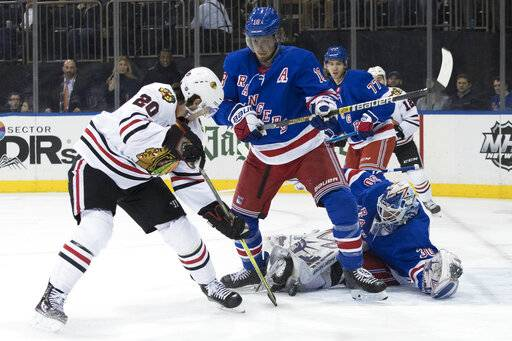 New York Rangers goaltender Henrik Lundqvist (30) and defenseman Marc Staal (18) defend against Chicago Blackhawks left wing Brandon Saad (20) during the first period of an NHL hockey game Thursday, Jan. 17, 2019, at Madison Square Garden in New York.
