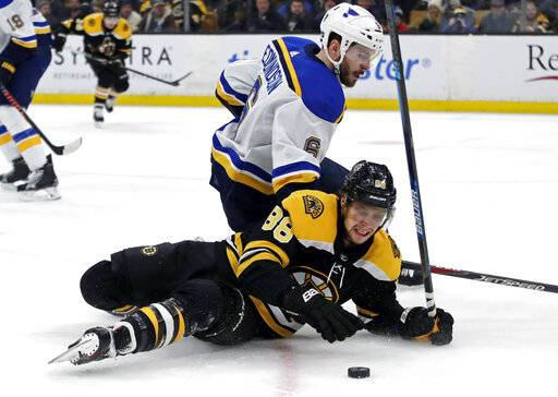 Boston Bruins right wing David Pastrnak (88) falls while chasing the puck against St. Louis Blues defenseman Joel Edmundson (6) during the second period of an NHL hockey game Thursday, Jan. 17, 2019, in Boston.