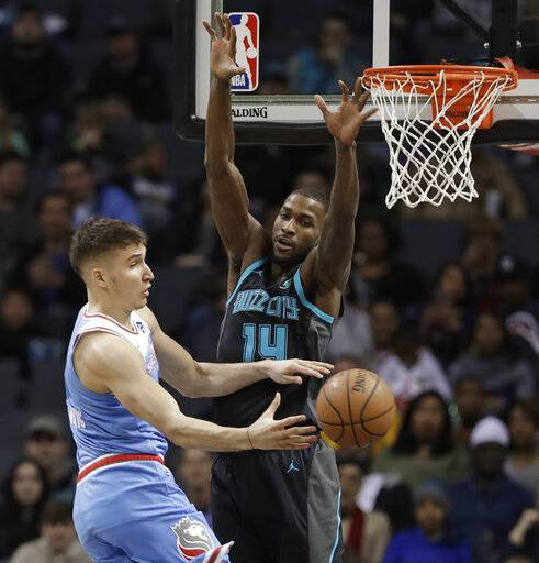 Sacramento Kings' Bogdan Bogdanovic, left, passes the ball as Charlotte Hornets' Michael Kidd-Gilchrist, right, defends during the first half of an NBA basketball game in Charlotte, N.C., Thursday, Jan. 17, 2019.