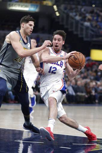 Philadelphia 76ers guard T.J. McConnell (12) drives on Indiana Pacers forward Doug McDermott (20) during the first half of an NBA basketball game in Indianapolis, Thursday, Jan. 17, 2019.