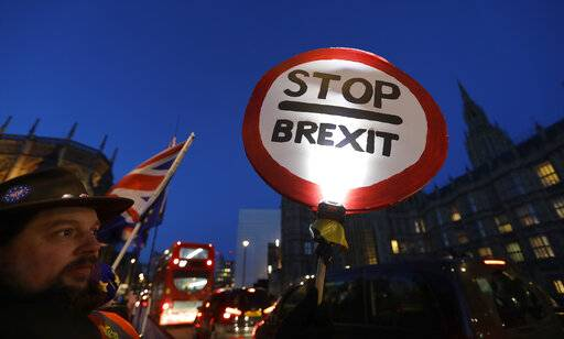 A pro European demonstrator holds a banner near parliament in London, Thursday, Jan. 17, 2019. British Prime Minister Theresa May is reaching out to opposition parties and other lawmakers Thursday in a battle to put Brexit back on track after surviving a no-confidence vote.