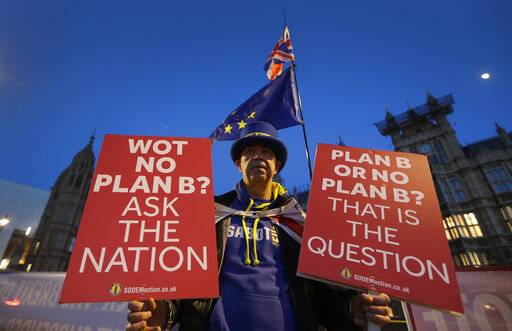 A pro European demonstrator holds banners near parliament in London, Thursday, Jan. 17, 2019. British Prime Minister Theresa May is reaching out to opposition parties and other lawmakers Thursday in a battle to put Brexit back on track after surviving a no-confidence vote.