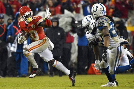 FILE - In this Jan. 12, 2019, file photo, Kansas City Chiefs wide receiver Tyreek Hill (10) gestures as he runs past Indianapolis Colts safety Clayton Geathers (26) and linebacker Anthony Walker during the second half of an NFL divisional football playoff game in Kansas City, Mo. The Chiefs, who play the New England Patriots on Sunday in the AFC championship game, have the pass-catching trio of speedy Hill, Sammy Watkins and sure-handed Travis Kelce.