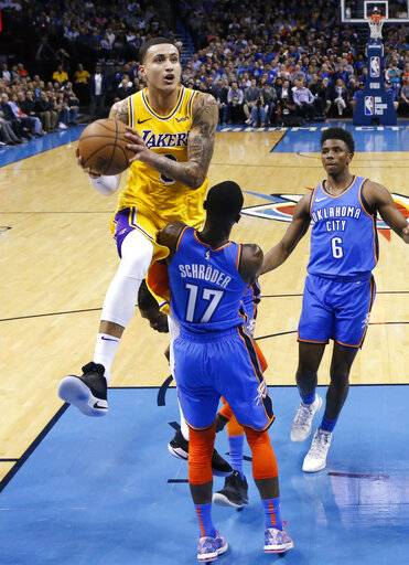 Los Angeles Lakers forward Kyle Kuzma (0) collides with Oklahoma City Thunder guard Dennis Schroeder (17) as he goes to the basket during the second half of an NBA basketball game in Oklahoma City, Thursday, Jan. 17, 2019. Thunder guard Hamidou Diallo (6) is at right.