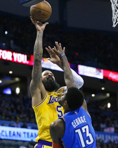 Los Angeles Lakers center Tyson Chandler (5) shoots over Oklahoma City Thunder forward Paul George (13) during the first half of an NBA basketball game in Oklahoma City, Thursday, Jan. 17, 2019.
