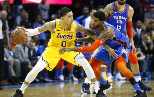 Oklahoma City Thunder forward Paul George, right, reaches for the ball held by Los Angeles Lakers forward Kyle Kuzma (0) during overtime of an NBA basketball game in Oklahoma City, Thursday, Jan. 17, 2019.