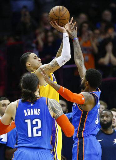 Los Angeles Lakers forward Kyle Kuzma, center, shoots between Oklahoma City Thunder center Steven Adams (12) and forward Paul George, right, during the second half of an NBA basketball game in Oklahoma City, Thursday, Jan. 17, 2019.